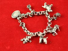 Silver charm bracelet with 7 charms.