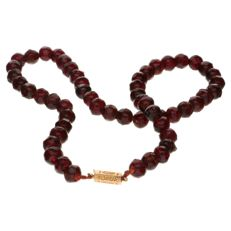 Glass garnet necklace set with yellow gold decorated clasp with floral pattern