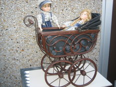 Old decorative doll's pram of wood and metal with 2 dolls