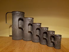 Set of 7 antique calibrated metal measuring cups.