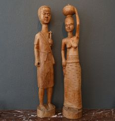 Two large carved wooden sculptures of an African man and woman