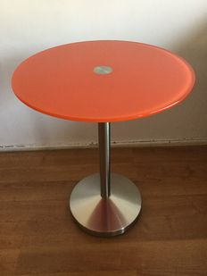 Side table in chrome with table top of hardened orange glass.