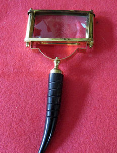 Magnifying glass made of brass with horn-like handle