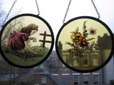 """Two stained glass round window pendants (suncatchers) """"The Playing Girl"""" and """"The Forest Flowers"""" marked FC"""