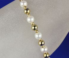 Pearl bracelet made of 14 kt gold links, strung with pearls and 14 kt gold ornaments
