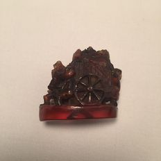 100% natural Amber carving of Chinese man leaning onto a wheel, about first 20 century
