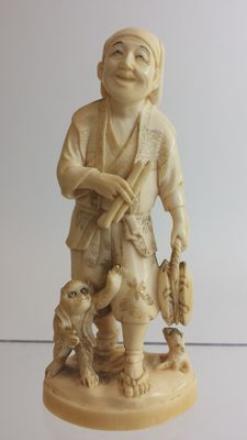 Ivory carving of an entertainer with a monkey, red seal to base - Japan - 19th century