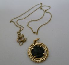 Set with a thin chain and gold and jet pendant.