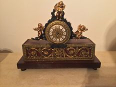 A mantel clock with putti, with bronze gold plated elements, around 1930