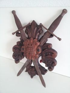 Wood carving featuring coat of arms with 2 metal swords