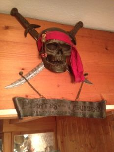 Pirate skull of wrought iron, crossed by 2 swords and accompanied by emblem with legend