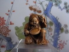 Ivory netsuke of Cheerful Okame combs her hair and looks at herself in the mirror  - Japan - ca. 1900 (late Meiji period)