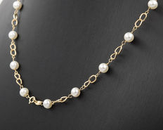Yellow gold choker interspersed with 18 Akoya round cultured pearls.