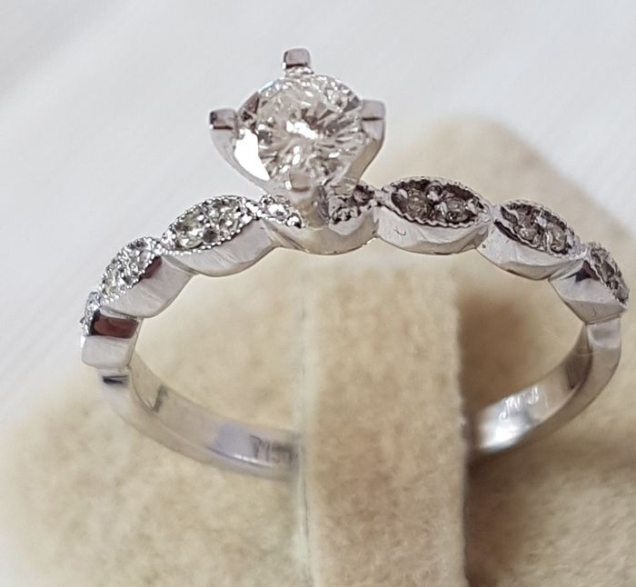 An 18 kt white gold ring with 1 brilliant cut diamond (0.31 ct) in the middle and 12 inlaid brilliant cut diamonds on the sides of the ring