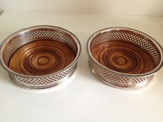 Two silver plated open work large wine bottle coasters with wooden bottom
