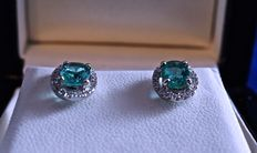 Two magnificent natural, oval and transparent emeralds of .60 ct each, mounted on rhodium-plated 18 kt white gold earrings with an entourage of diamonds of a brilliant cut of .24 ct in total.