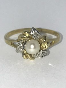 Classic 14 kt gold ring inlaid with an 0.03 ct diamond and a cultivated pearl.