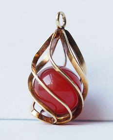 Gold pendant with an enclosed carnelian gemstone