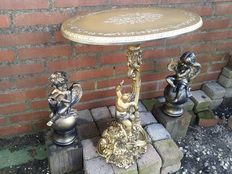 Heavy, tooled table in renaissance Baroque style and two loose putti angel statues