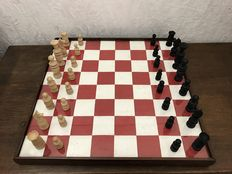 Chessboard with an oak frame, wooden chess pieces, dominoes set made of bone and wooden checkers pieces