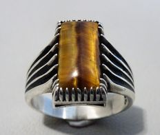Silver ring 925 with a tiger's eye baguette and ajour cut inside