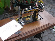 Singer pedal sewing machine complete with oak sewing table.