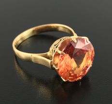 Yellow gold ring, 18 kt, adorned with a shining 6.2 ct orange Verneuil sapphire