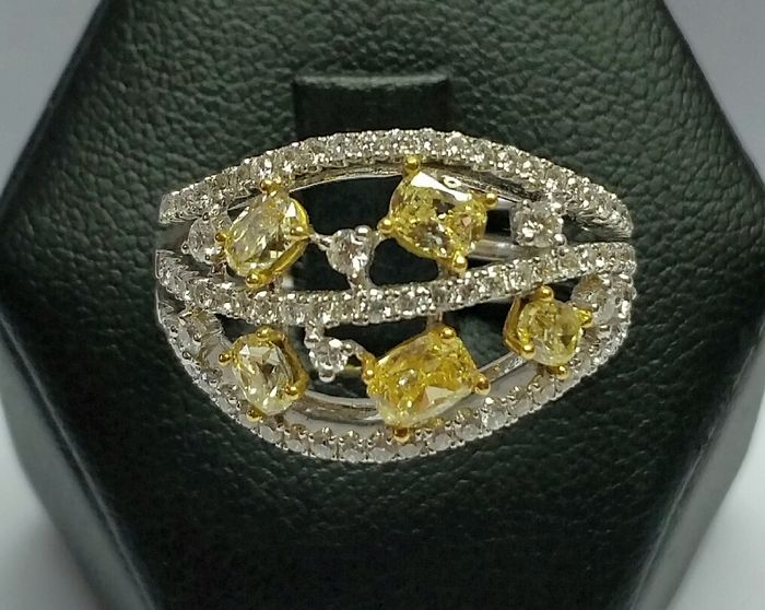 Ring with oval cut fancy yellow diamonds and brilliant cut white diamonds