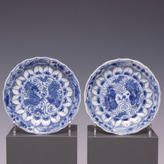 Blue/white porcelain dishes with 4-clawed dragons, surrounded by a lotus edge in relief – China – late 17th century (Kangxi period).