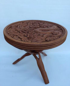 Wooden side table with carved top