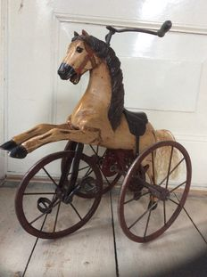 Beautiful nostalgic tricycle with horse made of wood