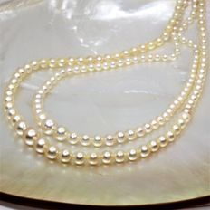 Antique cascading double-strand round salt water cultured pearl necklace with pearls of 3-8 mm in diameter.