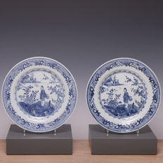 A nice pair of blue white porcelain plates with the decorations of a long rag doll with a flower basket