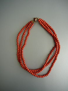 Three-rowed, red coral necklace with gold clasp.