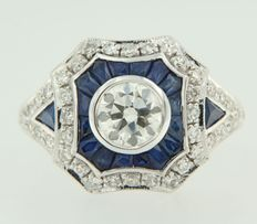 14 kt white gold ring set with old-Amsterdam cut central diamond of 0.91 ct, with entourage of 18 sapphires, 1.95 carat, and 40 single cut diamonds, 0.39 carat, ring size 17.25 (54)