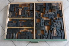 Old letter tray from a letter cabinet of a printing company, with approximately 175 original block letters.