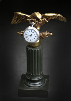 Empire watch case in bronze and brass. Eagle tenant a branch on column.