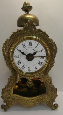 Small standing luxury alarm clock with decorations and visible pendulum by the brand Japy of around 1900