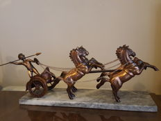 A coppered metal model of a Roman warrior riding in a chariot with four horses and mounted to a rectangular marble base.