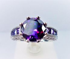 925 silver ring with a large brilliant cut amethyst and small princess cut amethysts.