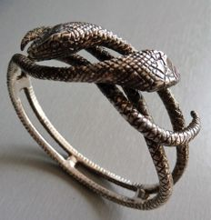 Large engraved solid silver bracelet depicting two intertwined snakes.