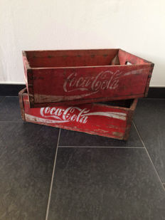Two original red - coloured wooden Coca Cola crates from America.