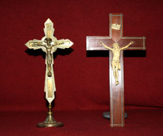 Lot of 2 crucifixes: 1 of yellow copper, 1 of precious wood with body of Christ of synthetic material (?) or ivory (?) - the middle of last century