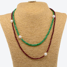 Double-strand station necklace: one strand composed of emerald beads and cultured pearls, and the other strand composed of ruby beads and cultured pearls. With clasp in 18 kt (750/1000) yellow gold.