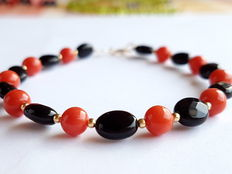 Bracelet made of 100% natural red coral pearls, onyx, with 585/1000kt yellow gold clasp and inbetween-beads made of 585/1000 yellow gold.