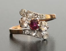 Art Nouveau ring in 18 kt gold, luminous central ruby surrounded by two diamonds, with rose pavé setting (total 0.5 ct)