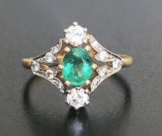 Art Nouveau 'You and Me' ring in 18 kt gold, adorned with an oval cut emerald, and sublime brilliant-cut H/VVS diamonds