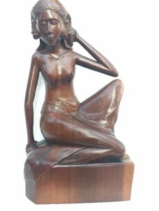 Wood carving in Art Deco style of a woman in a seated pose –Bali –Indonesia