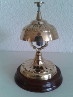Tall brass hotel bell - counter top bell on a wooden base.