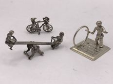 Old Dutch scene of 3 Dutch silver silver miniatures depicting children on a seesaw, child with a hoop, and a bicycle.